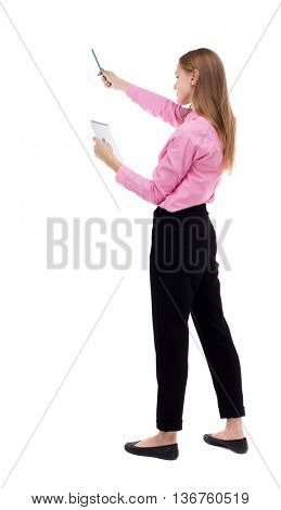 back view of  stands woman takes notes in a notebook. girl  watching. Rear view people collection.  backside view of person. Woman office worker in a pink shirt looks to notebook pen showing up.