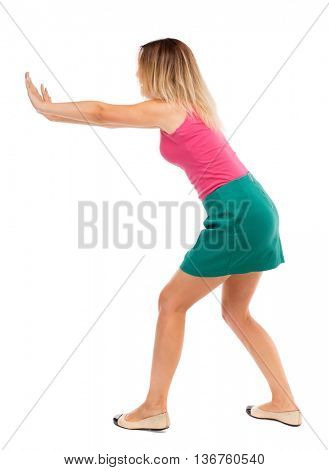 back view of woman pushes wall. Isolated over white background. Rear view people collection. backside view of person. Blond girl in a green skirt pushing something heavy right.
