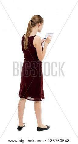 back view of  stands woman takes notes in a notebook. Rear view people collection.  backside view of person.  Isolated over white background. A girl in a burgundy dress writes in a notebook.
