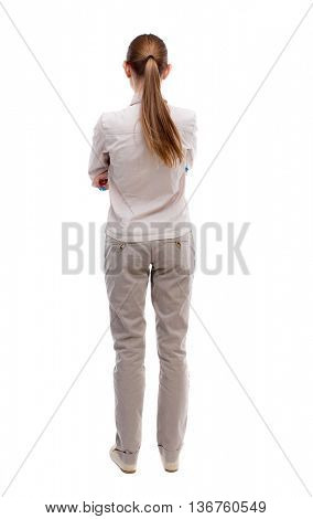 back view of standing young beautiful  woman.  girl  watching. Rear view people collection.  backside view of person.  Girl with long hair in white jacket standing with her hands folded on his stomach