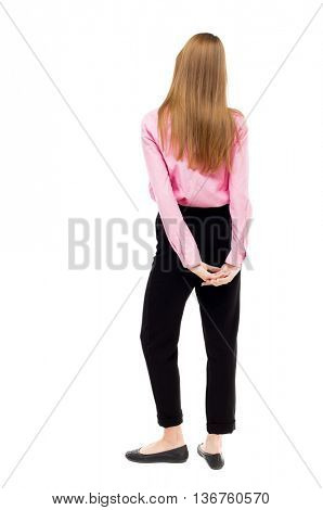 back view of standing young beautiful  woman.  girl  watching. Rear view people collection.  backside view of person. Isolated over white background. A girl in pink shirt holding hands behind his back