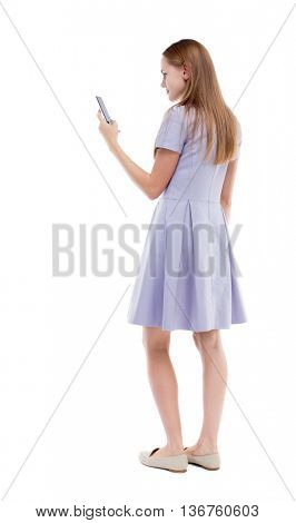 back view of standing young beautiful  woman  and using a mobile phone. girl  watching. The girl in a blue dress is looking at the screen of your smartphone.