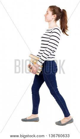 Girl comes with  stack of books.back view. Rear people collection.  backside of person.  Isolated over white background. Girl in white striped sweater unhappy carries the book to the right.