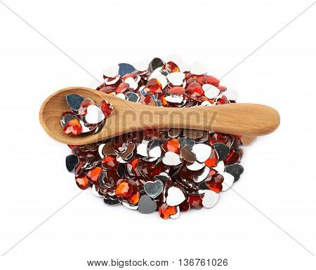 Pile of multiple heart shaped red glossy scrapbooking acrylic beads with the wooden spoon over it, composition isolated over the white background