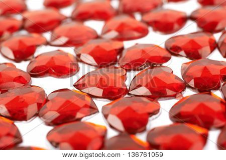 Surface covered with the red glossy scrapbook heart beads as a background composition