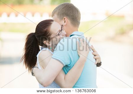 Couple Meeting On The Street And Embracing One Another Tightly