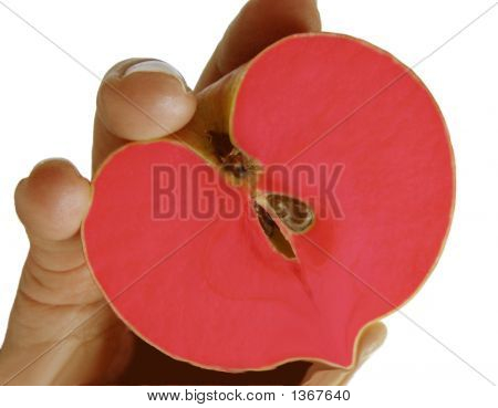 A Women'S Hand Holding A Cut Apple In The Fotm Of A Heart