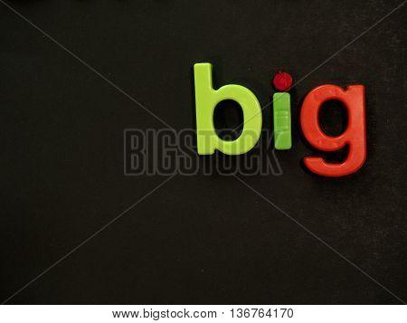 Big! Vibrant word in magnet letter on black background