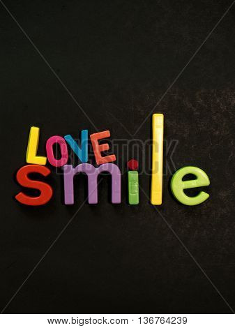 Love and smile! Inspirational message in vibrant colorful magnet letters on black background