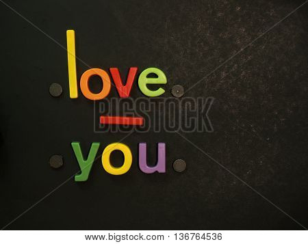 Love you! Inspirational message in vibrant colorful magnet letters on black background
