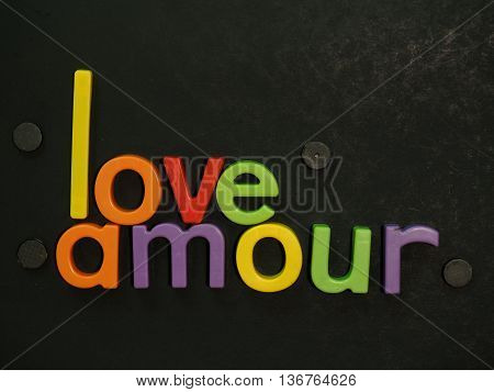 Love Amour! Inspirational message in vibrant colorful magnet letters on black background