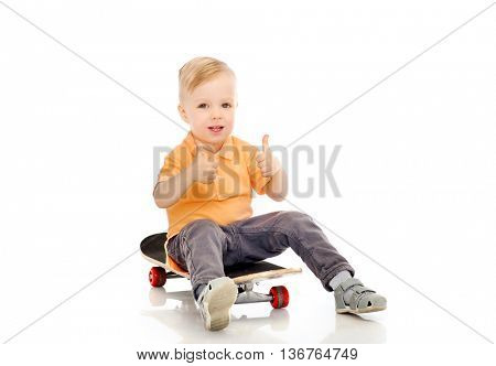 childhood, sport, leisure, gesture and people concept - happy little boy sitting on skateboard and showing thumbs up