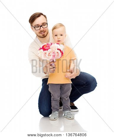 family, childhood, fatherhood, holidays and people concept - happy father and and little son with bunch of flowers