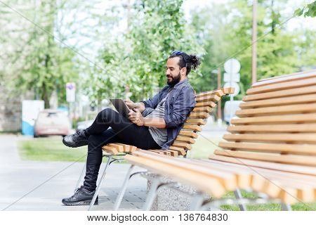 leisure, technology, communication and people concept - man with tablet pc computer sitting on city street bench