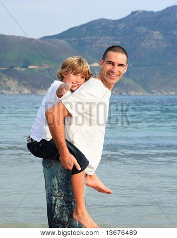 Father giving his son piggyback ride on the beach smiling