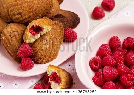 French pastry Madeleine with raspberries. Selective focus.