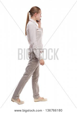 side view of a woman walking with a mobile phone.  backside of person.  Rear people collection. Isolated over white background. A girl in a white jacket walking slowly pressed phone to his ear