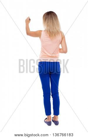 back view of writing beautiful woman. Rear people collection.  backside of person. Isolated over white background. Blonde in blue trousers draws felt-tip pen in front of you on the board.