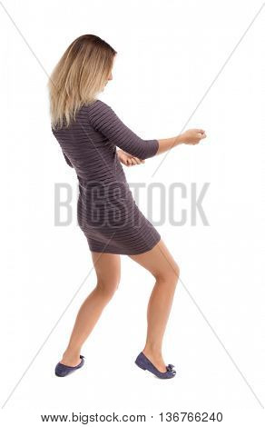 back view of standing girl pulling a rope from the top or cling to something. girl  watching. Rear people collection.  Isolated over white background. Blonde in a short dress pulls the rope on left.
