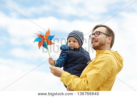 family, childhood, fatherhood, leisure and people concept - happy father and little son with pinwheel toy outdoors