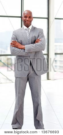Smiling businessman with folded arms looking at the camera