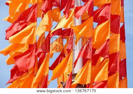 Festive flags of red and orange color on a flagstaff