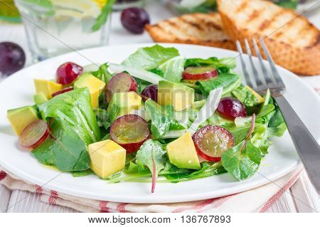 Vegetarian salad with avocado grape rucola onion with vinegar dressing on white plate horizontal