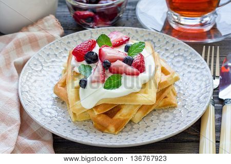 Homemade belgian waffles with yogurt strawberry and blueberry breakfast time horizontal