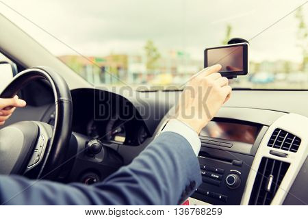 transport, business trip, technology, navigation and people concept - close up of male hand using gps navigator while driving driving car