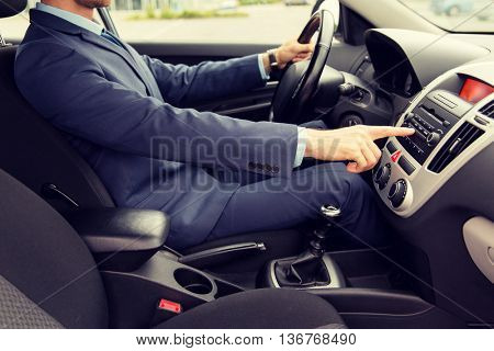 transport, business trip, technology and people concept - close up of young man in suit driving car and adjusting music volume on control panel stereo system