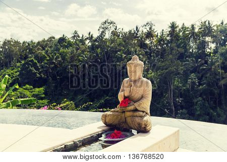 travel, vacation, tourism, religion and luxury concept - beautiful view from infinity edge pool with buddha statue to tropical woods in asia