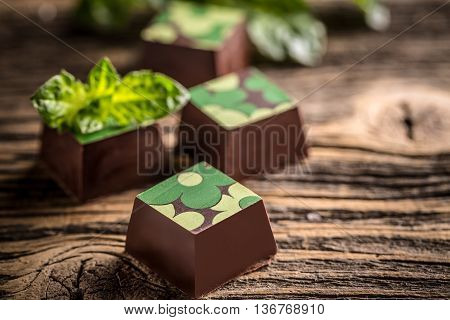 Delicious chocolate pralines on vintage wooden background