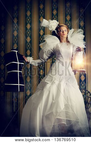 Beautiful fashion model in the refined white dress and mannequin. Vintage style. Art project. Haute Couture.
