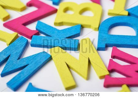 White surface covered with the multiple colorful painted wooden letters as a backdrop composition