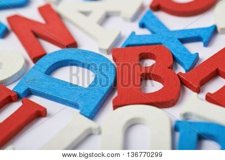 White surface covered with the multiple colorful red, blue, white painted wooden letters as a backdrop composition