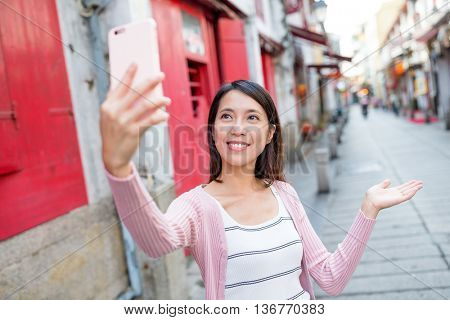 Woman using mobile phone to take selfie