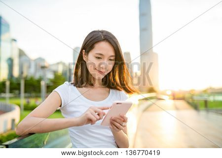 Woman looking at mobile phone at sunset