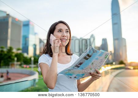 Woman using city map and calling on cellphone