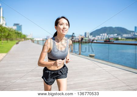 Young woman running on boardwalk