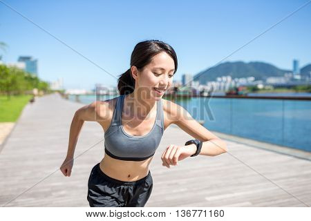 Woman using smart watch when running at city