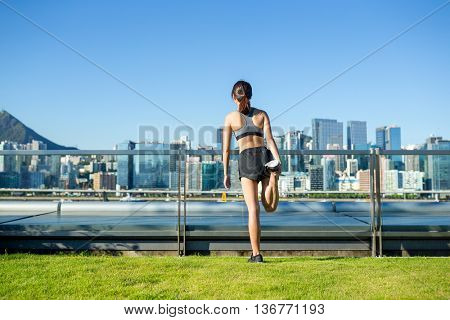 The back view of woman doing warm up exercise at city