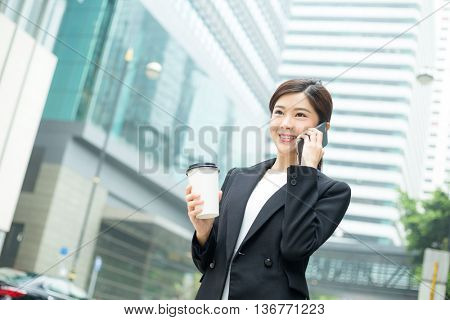 Businesswoman talking to cellphone and holding coffee