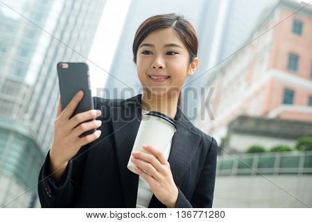 Business woman use of cellphone and holding a coffee