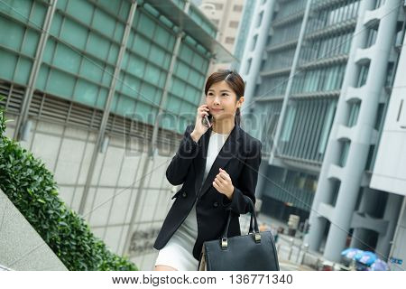 Business woman talk to mobile phone and walking outdoor