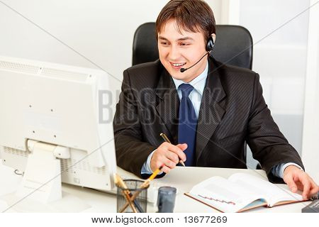 Smiling business man with headset sitting at office desk and looking at computer monitor
