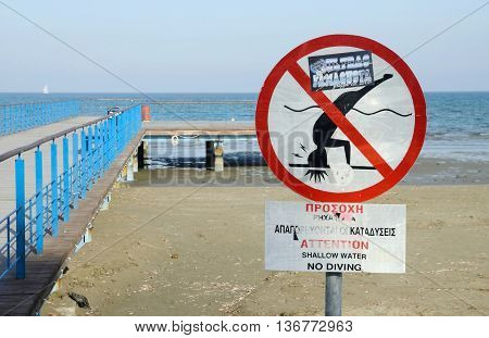 LARNACA CYPRUS - APRIL 7 2016: view of Larnaca Phinikoudes beach with red no jumping warning sign on April 7 in Larnaca Cyprus.Larnaca - is a city on southern coast and capital of eponymous district.