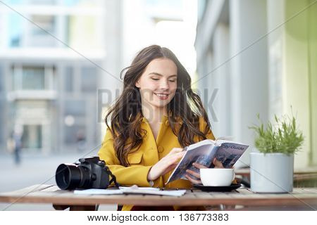 travel, tourism, leisure and people concept - happy young tourist woman or teenage girl with guide book and digital camera drinking cocoa at city street cafe terrace