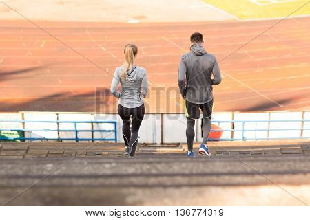 fitness, sport, exercising and lifestyle concept - couple running downstairs on stadium