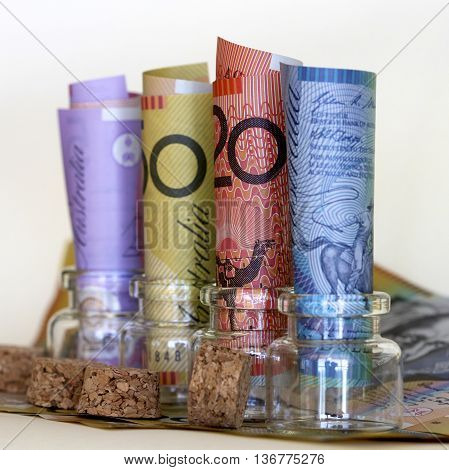 Australian notes in glass jars (focus on red $20 note)