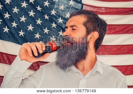 Ukraine Kyiv - July 27 2016: young patriotic happy bearded man with long blue beard on american flag background drinking coca cola from bottle outdoor celebrating independence day usa